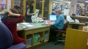 Joan Vertefeuille, right, worked at the new circulation desk during the 2012 open house.